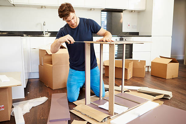 Man assembling furniture in his new home stock photo