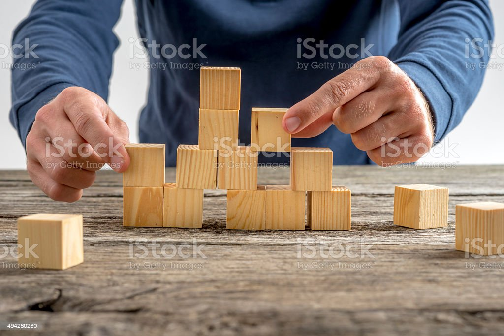 Man Assembling Wooden Cubes on Table stock photo