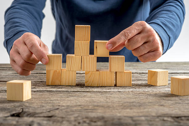 man assembling wooden cubes on table - stability stock photos and pictures