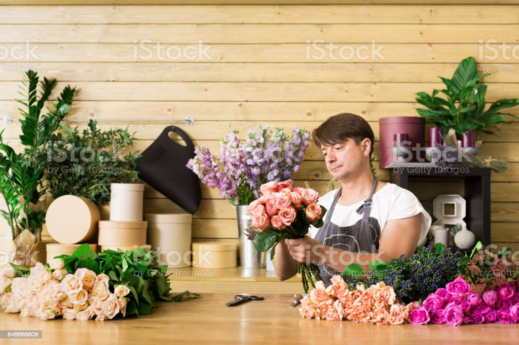 Small business. Male florist making rose bouquet at counter desk in...