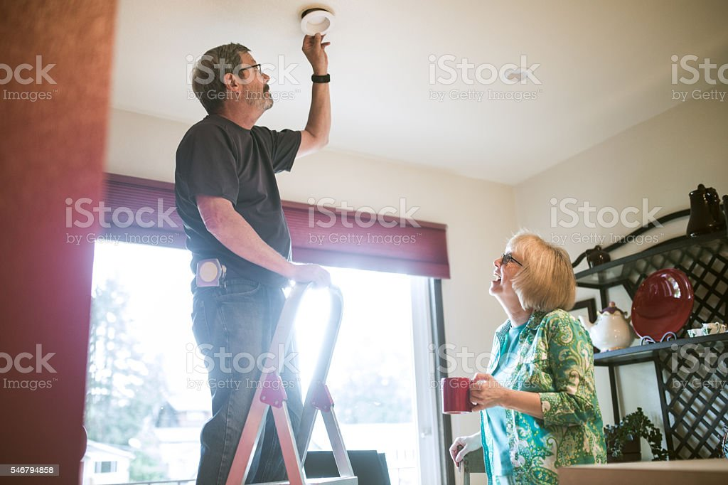 Man Assists Senior Woman With Chores stock photo