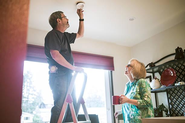 man assists senior woman with chores - glühbirne auswechseln stock-fotos und bilder