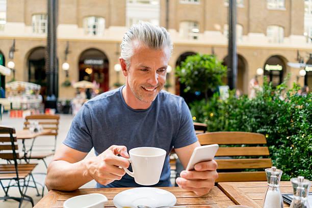 man at a cafe texting on his phone - schöne englische wörter stock-fotos und bilder