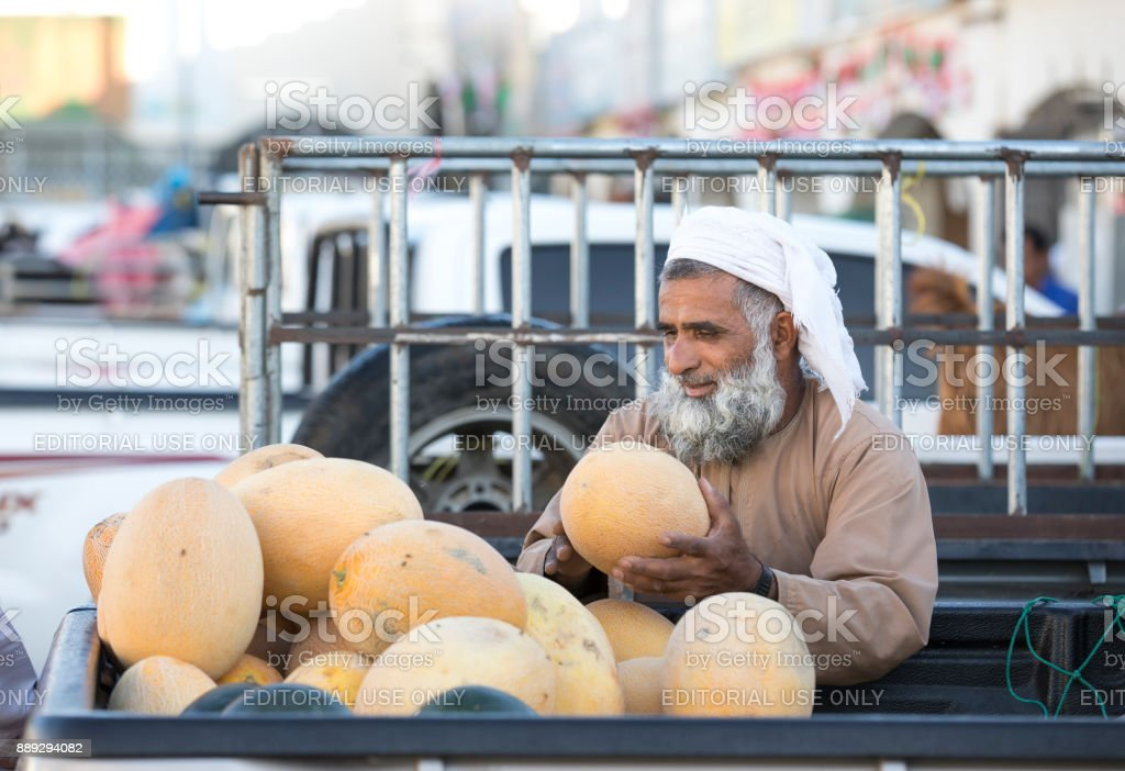 man at a market selling melons stock photo