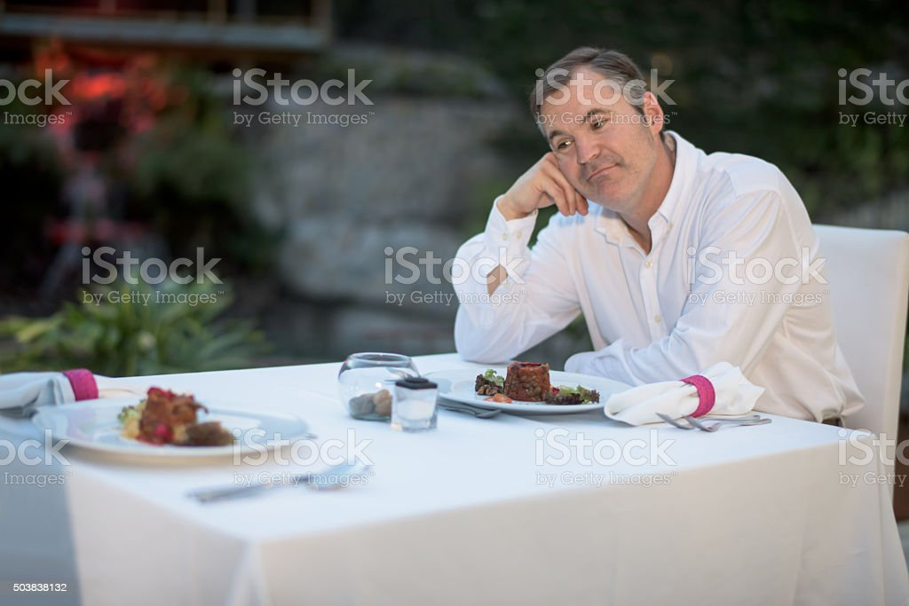 Man at a restaurant being stood up stock photo