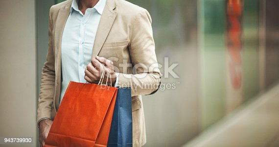 Closeup front view of an unrecognizable mid adult man walking through a shopping mall and carrying some shopping bags. Copy space on the right hand side.