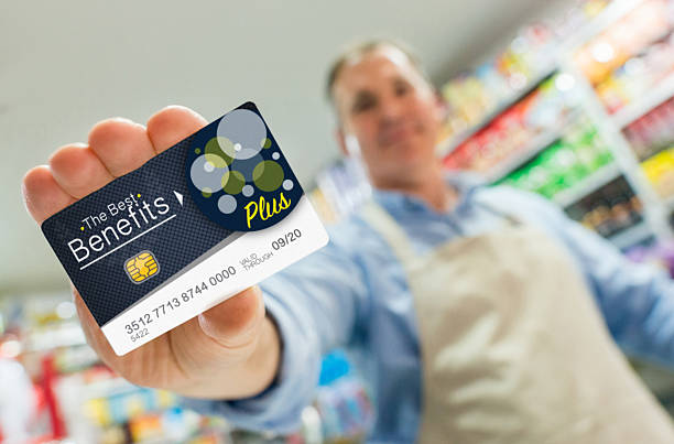 man at a store holding a loyalty card - gutscheinkarten stock-fotos und bilder