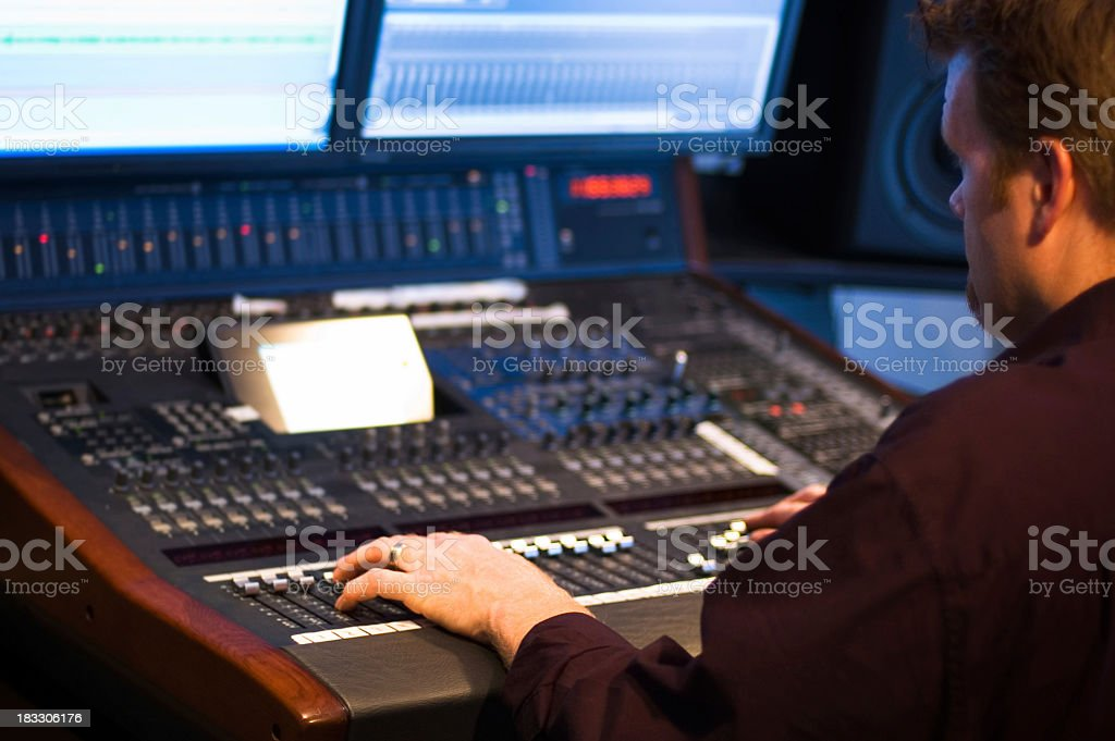 Man at a studio control moving buttons up and down stock photo