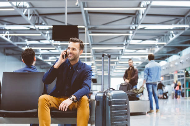 man at airport lounge and using mobile phone - business travel stock photos and pictures