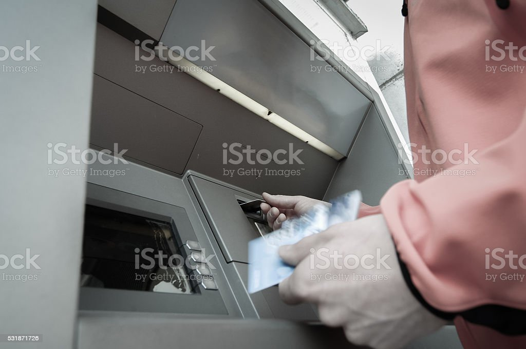 Man at ATM machine with stash of credit cards stock photo