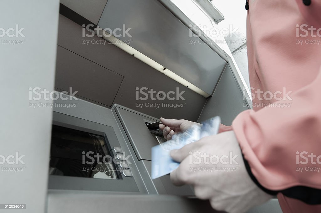 Man at ATM with stash of credit and debit cards stock photo