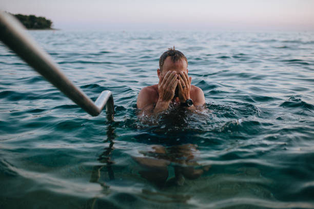 Hombre en la playa al atardecer tomando un baño en el océano azul - foto de stock