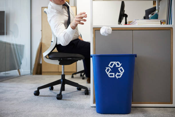 man at desk throwing screwed up paper into recycling bin - bin stock pictures, royalty-free photos & images