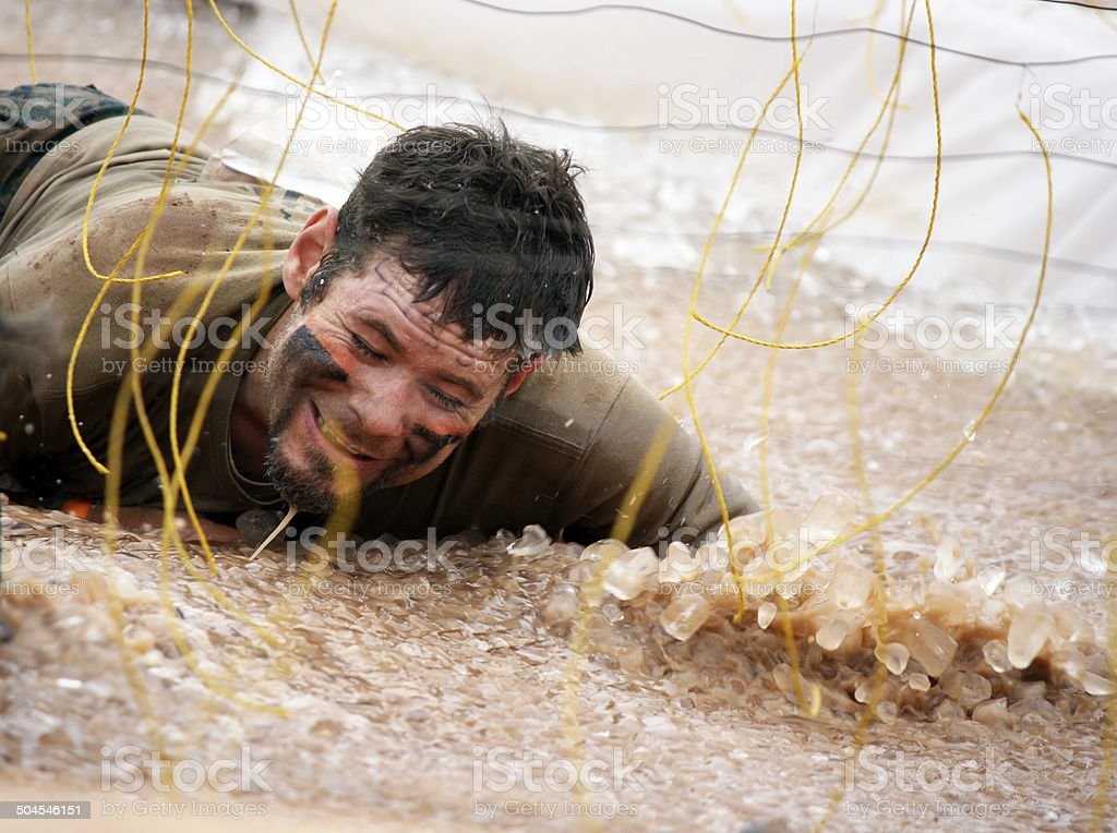 man at electric shock obstacle during mud run event stock photo