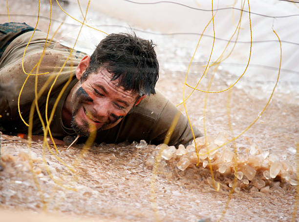 man at electric shock obstacle during mud run event A man is submerged in mud and ice while going under the electric shock tentacles at a mud run obstacle course event mud run stock pictures, royalty-free photos & images