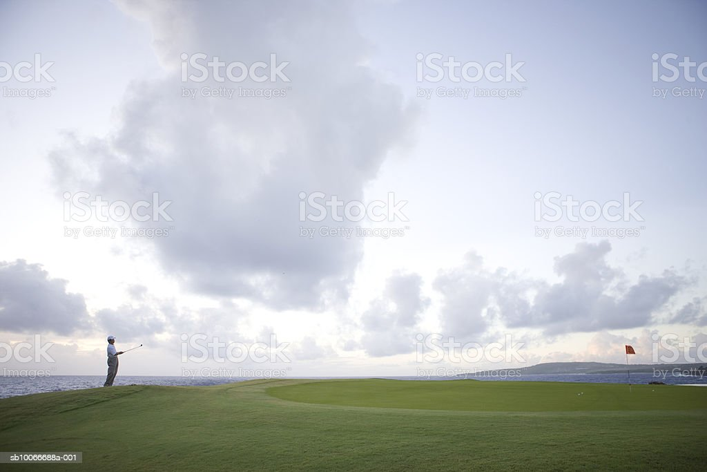Man at golf course holding golf club, looking away royalty-free stock photo