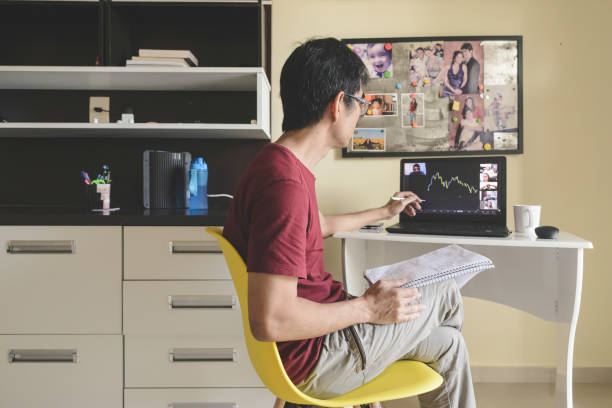 Man at home analyzing a stock trading chart in a video conference with group of investors stock photo