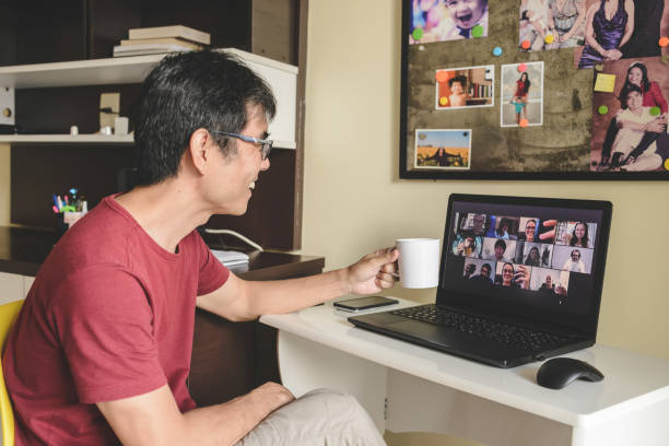 Man at home attending to a virtual happy hour with many people on screen toasting online together stock photo