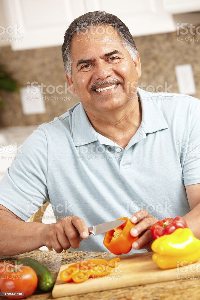 Man at home chopping vegetables stock photo
