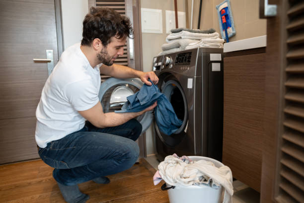 Man at home doing the laundry stock photo