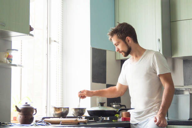 a man at home is cooking - cooker happy imagens e fotografias de stock