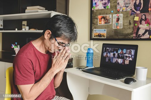 Man at home joining a group of people online praying together in a video conference