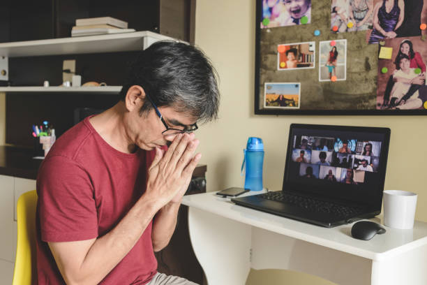 Man at home joining a group of people online praying together in a video conference stock photo
