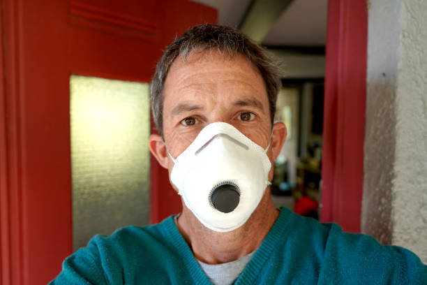 Man at home wearing face mask for Coronavirus stock photo