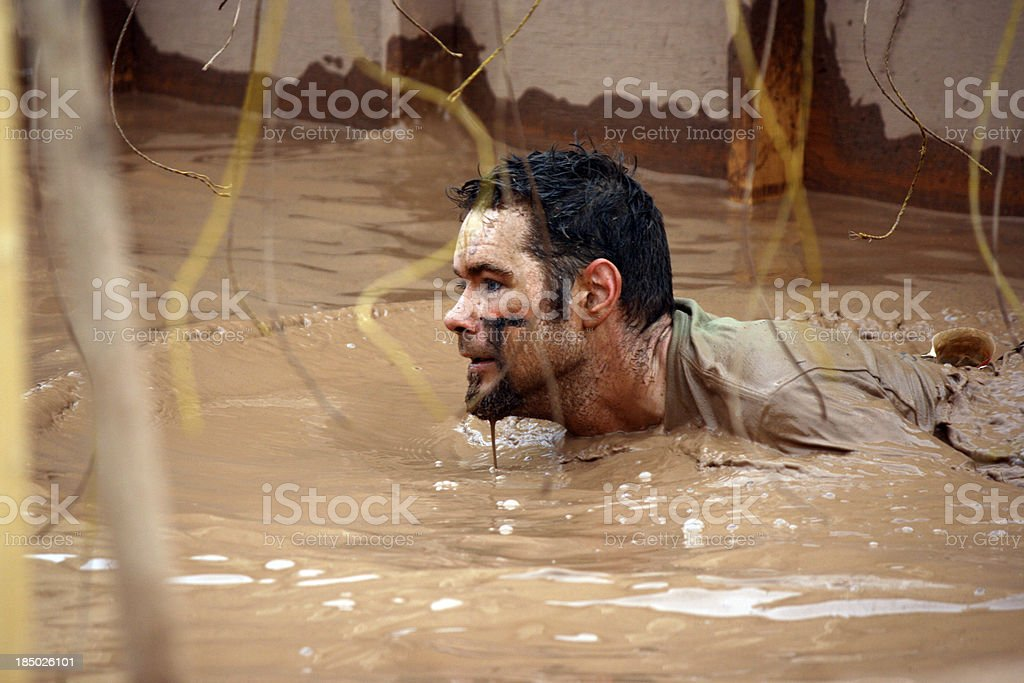man at mud run obstacle course stock photo
