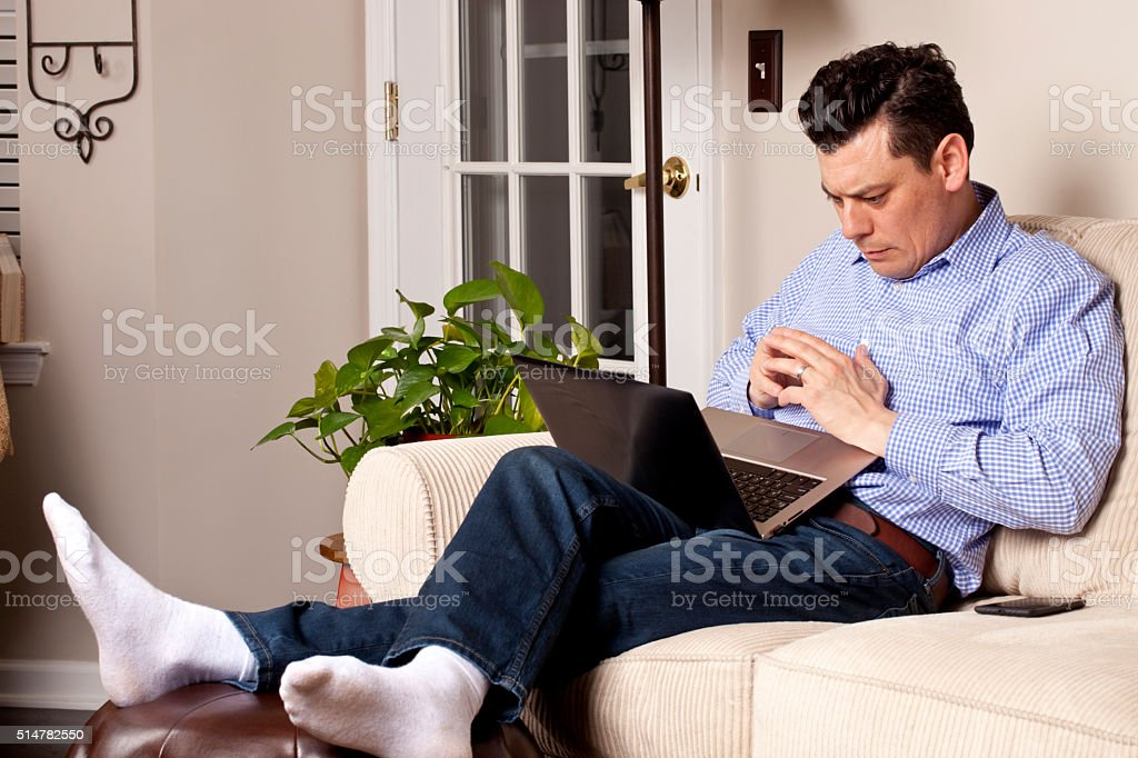Man at on couch relaxing, feet up engrossed in laptop stock photo