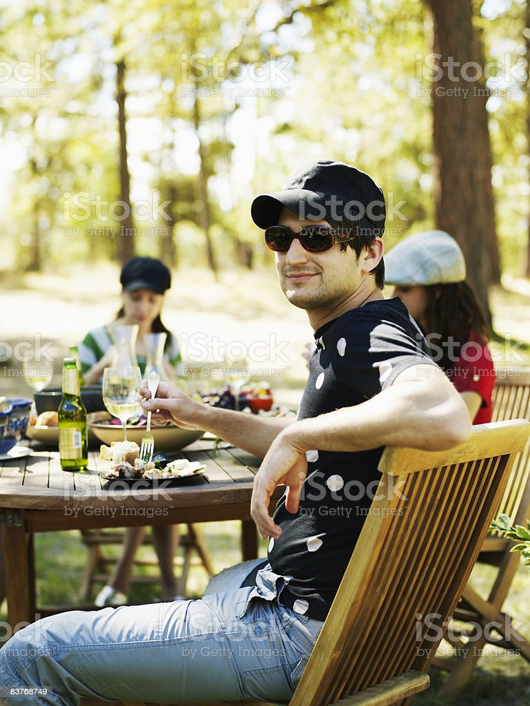Man at outdoor dining table with friends royalty-free stock photo
