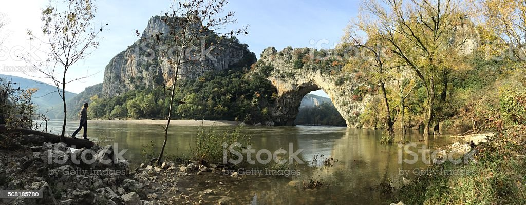 Man at Pont d'Arc (Ardéche) in autum with high water stock photo