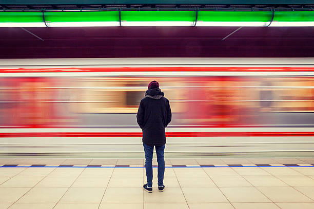 Man at subway station and moving train Lonely young man shot from behind at subway station with blurry moving train in background subway platform stock pictures, royalty-free photos & images