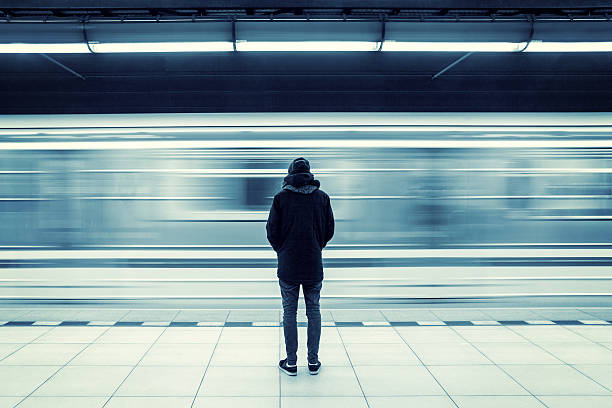 Man at subway station Lonely young man shot from behind at subway station with blurry moving train in background subway platform stock pictures, royalty-free photos & images