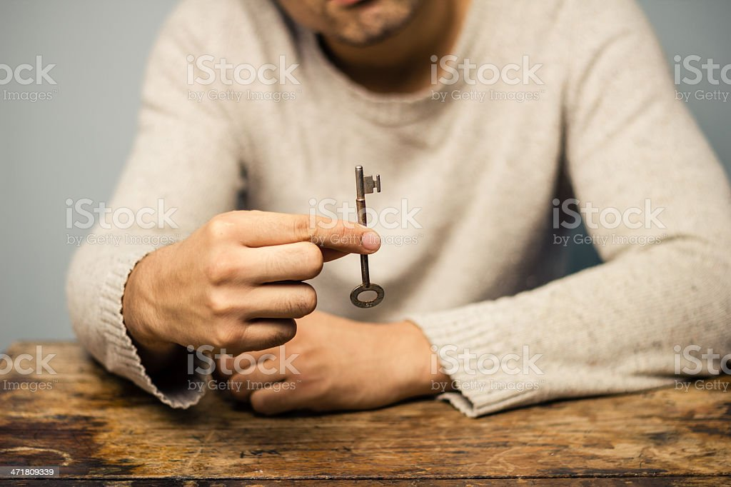 Man at table holding a key royalty-free stock photo