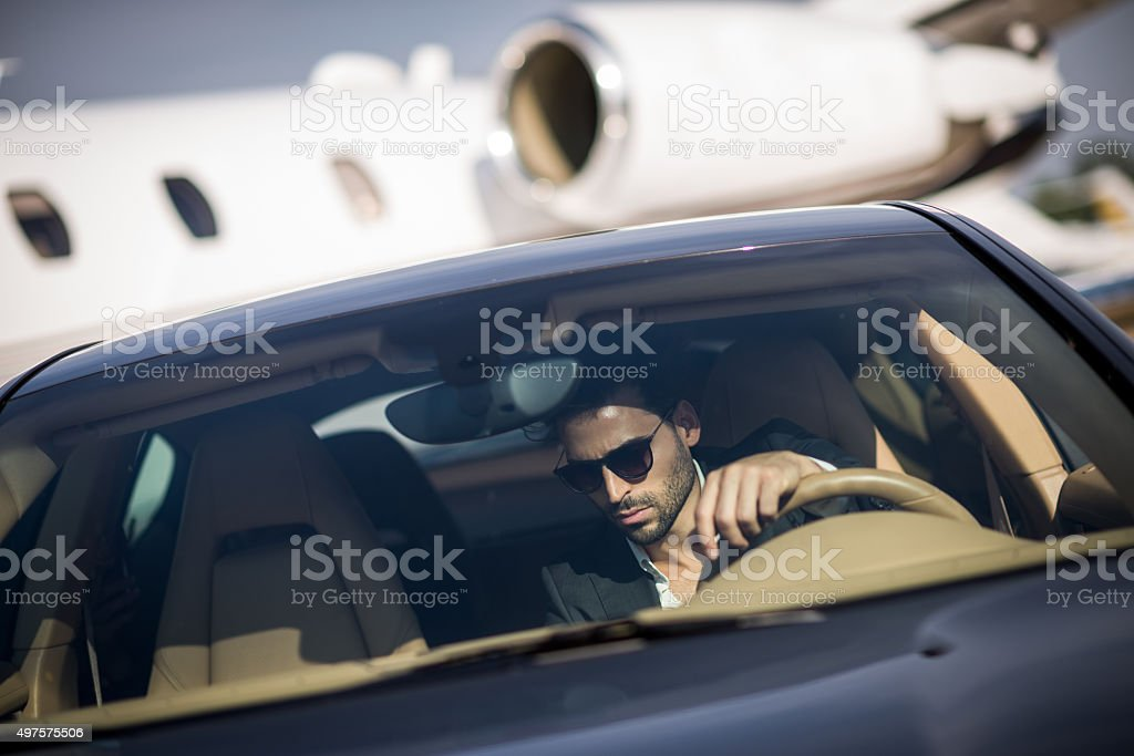 Man at the airport sitting in his car stock photo