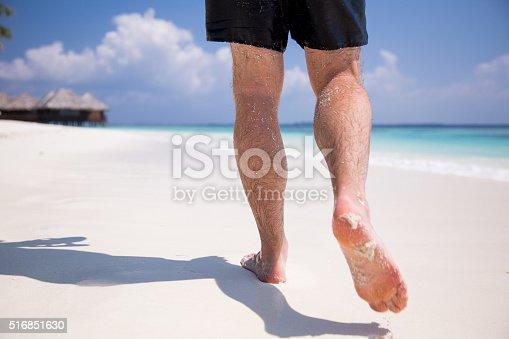174919648 istock photo Man at the beach 516851630