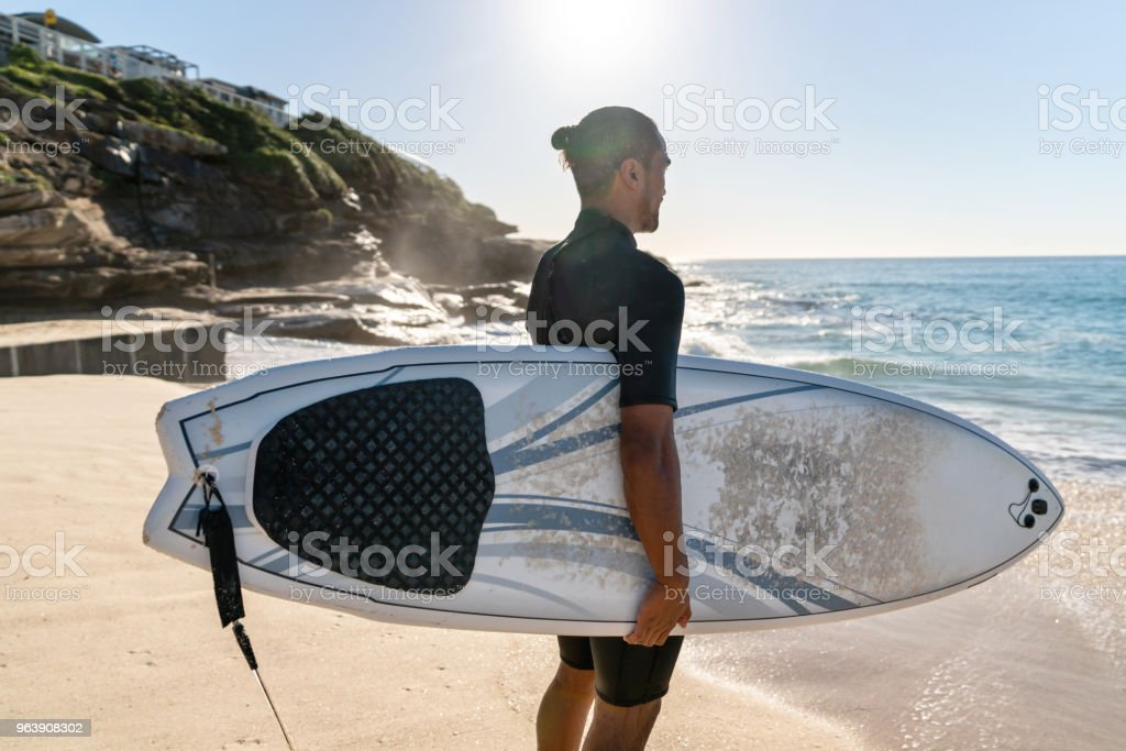 Man at the beach surfing and carrying his board - Royalty-free Adult Stock Photo