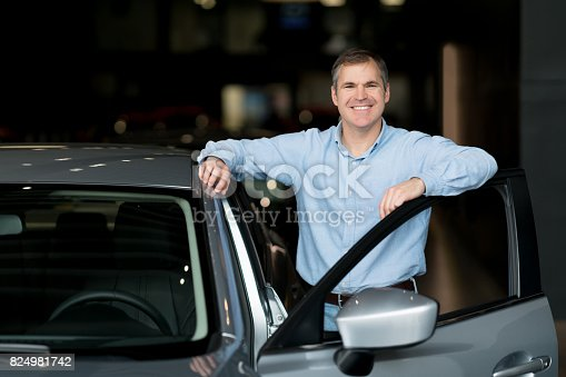 1138561232 istock photo Man at the dealership buying a car 824981742
