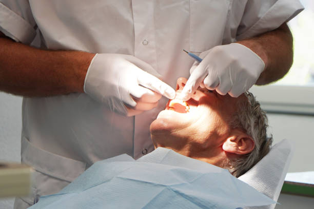 Man at the dentist, having his teeth checked Caucasian Man at the dentist, having his teeth checked. Hands with gloves holding a mirror in hand, touching the teeth tooth crown stock pictures, royalty-free photos & images