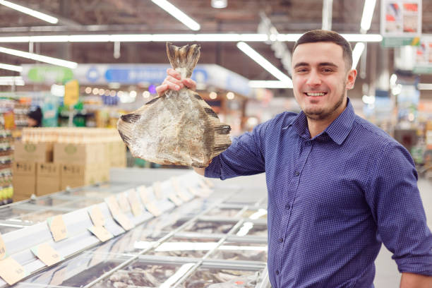 man at the grocery store with frozen flounder fish. - banchi di pesci foto e immagini stock