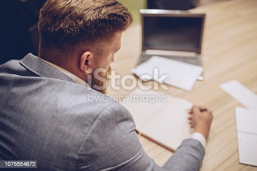 istock Man at the office writing in textbook 1075554672