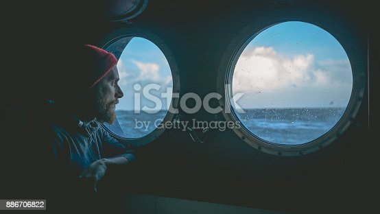istock Man at the porthole window of a vessel in a rough sea 886706822