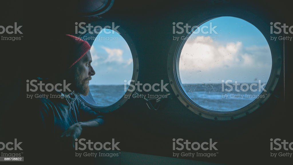 Homme à la fenêtre hublot d'un navire dans une mer agitée - Photo