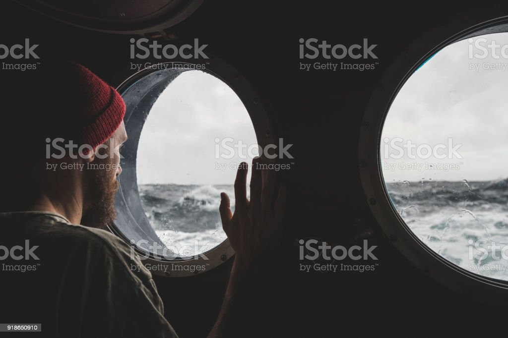 Man at the porthole window of a vessel in a rough sea stock photo