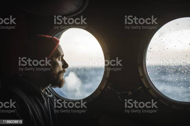 Man at the porthole window of a vessel sailing the sea picture id1159026913?b=1&k=6&m=1159026913&s=612x612&h=fahwwkn9o08oyseo8yekuqmisgqk1dybp uaxb6wmxy=