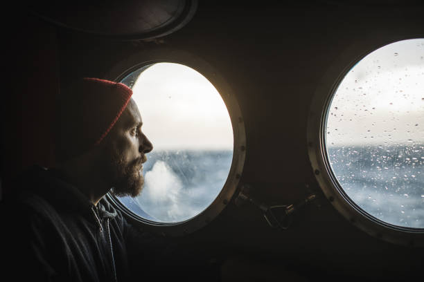 Man at the porthole window of a vessel sailing the sea Man at the porthole window of a vessel sailing the sea sailor hat stock pictures, royalty-free photos & images