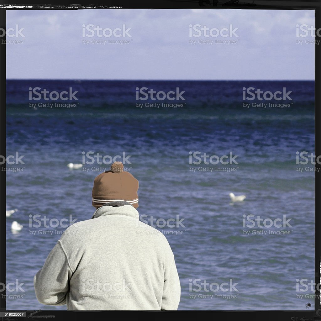 man at the sea in winter stock photo