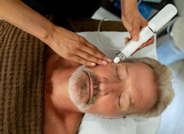 顔レーザー治療スパで男 ストックフォト