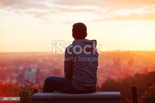 Young man is looking at the sunrise
